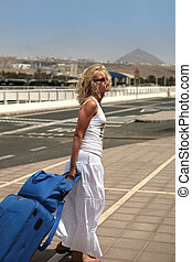 Pretty young woman traveling with a suitcase