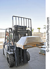 Man driving a forklift moving a heavy load