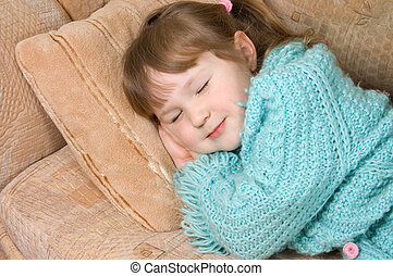 The little girl sleeps on a sofa