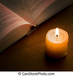Book in candlelight - Open book and burning candle on dark