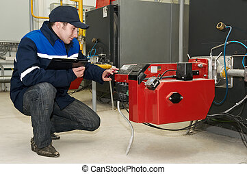heating engineer works with boiler