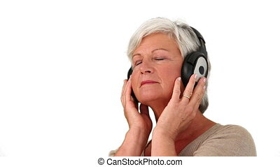 Senior woman listenning music isolated on a white background