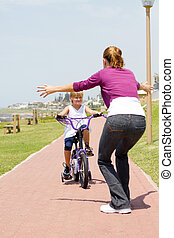 happy little girl riding a bike toward her mother