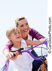 happy mother teaching girl bicycle - low angel view of happy...