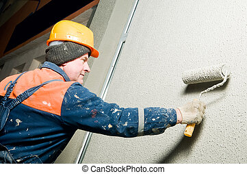 builder plastering facade wall - facade worker at decoration...