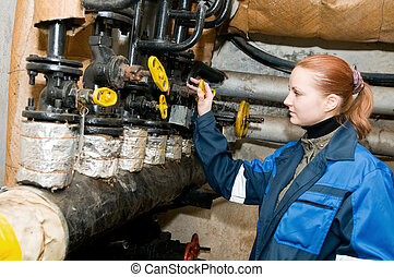 woman engineer in a boiler room - woman engineer adjusting...