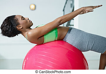 african woman doing series of sit-ups in gym - young african...