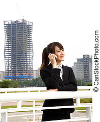 Happy asian business woman talking on the phone and office...