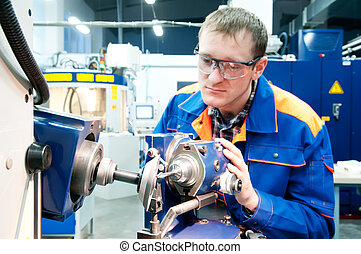 worker at machine tool operating - worker in uniform and...