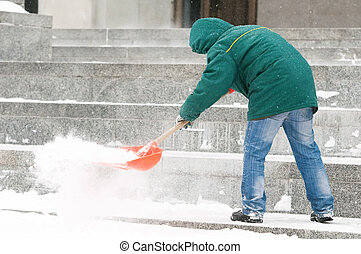 Man shoveling snow - communal services worker in uniform...