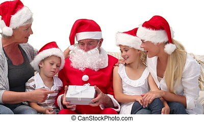 Santa Claus giving gifts to a family on the sofa