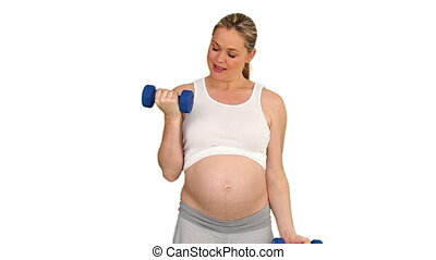 Pretty pregnant woman with dumbbells