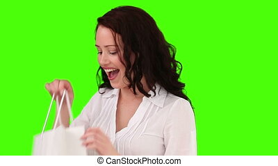 Brunette taking clothes out from her shopping bag -...