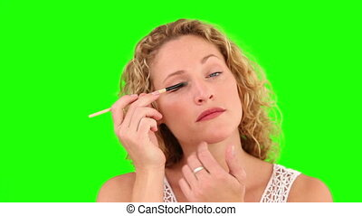 Curly blond haired female putting on make-up