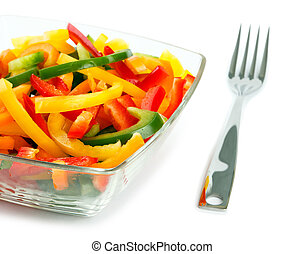 Mix of fresh vegetables from a color paprika in a glass plate on a white background with a plug