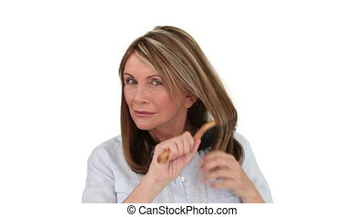 Senior woman tidying her hair - Senior woman tidying on her...