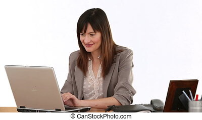 Businesswoman laughing in front of her laptop