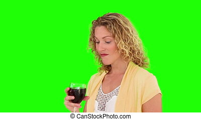 Curly blond haired female enjoying a glass of red wine -...