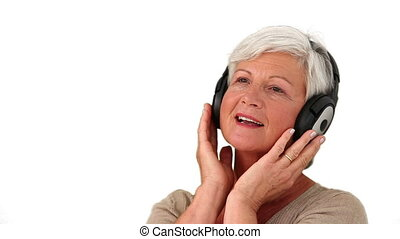 Senior woman listenning music against a white background