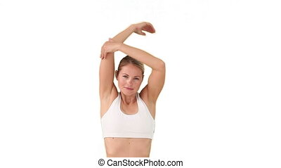 Blond woman in sportswear stretching isolated on a white...