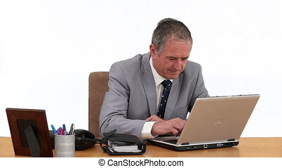 Elderly businessman in gray suit working on his computer