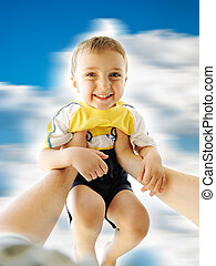 Very happy little cute boy up in his father's arms, rotating together: love, happiness and care