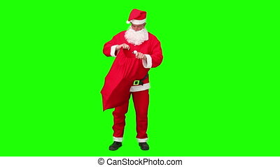 Santa Claus taking a gift in his bag against a green screen