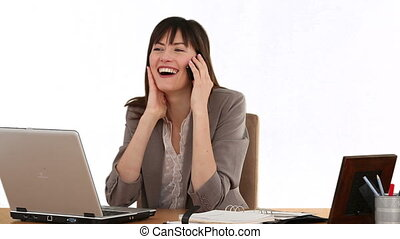 Businesswoman laughing on the phone at her desk