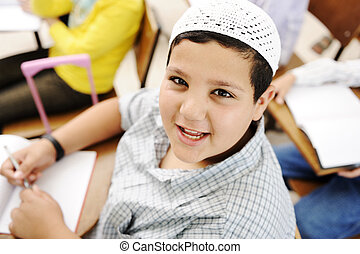 Very positive kid with white small hat sitting on desk in classroom and smiling