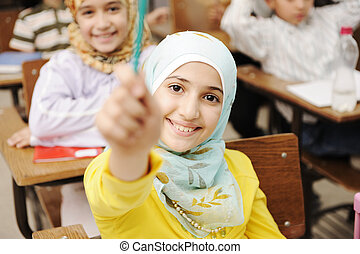 Adorable Muslim girl in classroom with her friends children...