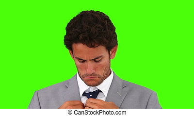 Young businessman wearing a suit and putting on his tie -...