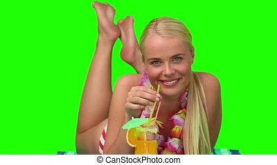 Blond female in swimsuit sipping a cocktail on the beach -...