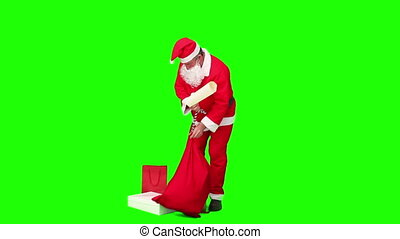 Santa Claus checking his list of gifts against a green...