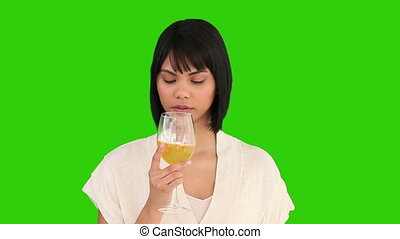 Chinese female enjoying a glass of white wine against a...