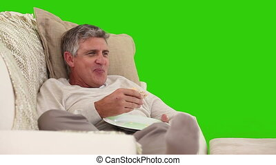 Retired man eating a sandwich in front of the tv
