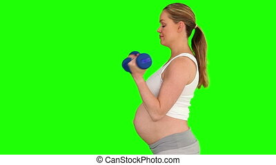 Pregnant lady with dumbbells against a green screen