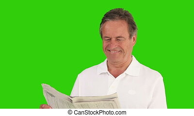 Elderly man laughing in front of a newspaper