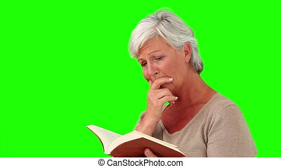 Mature woman crying in front of a book against a green...