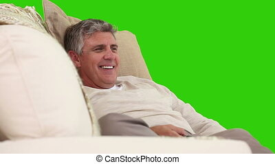 Middle-age man watching TV in his sofa