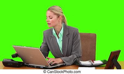 Blond businesswoman working at her desk