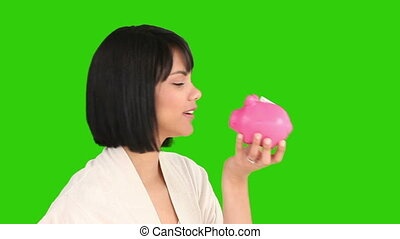Chinese female saving up money against a green screen
