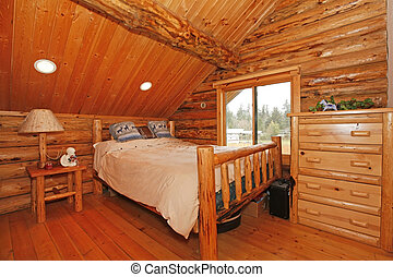 Bedroom in rustic mountain log cabin with large scale...