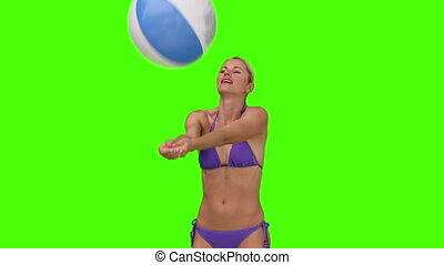 Female in purple swimsuit playing with a ball