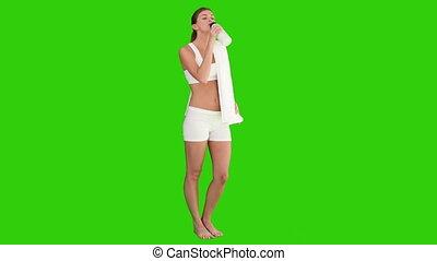 Dark haired female in sportswear drinking water after sport...