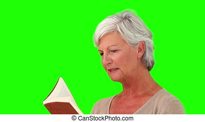 Senior woman reading a book against a green screen