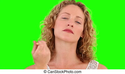 Curly blond haired female putting on make-up against a green...