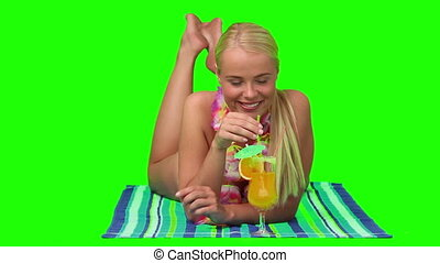 Cute blond female in swimsuit sipping a cocktail -...