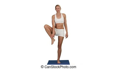 Pretty woman in sportwear doing yoga on a ground cloth