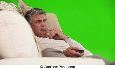 Middle-age man  watching tv on his sofa