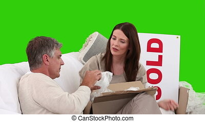 Couple unpacking crokery in the living room against a green...
